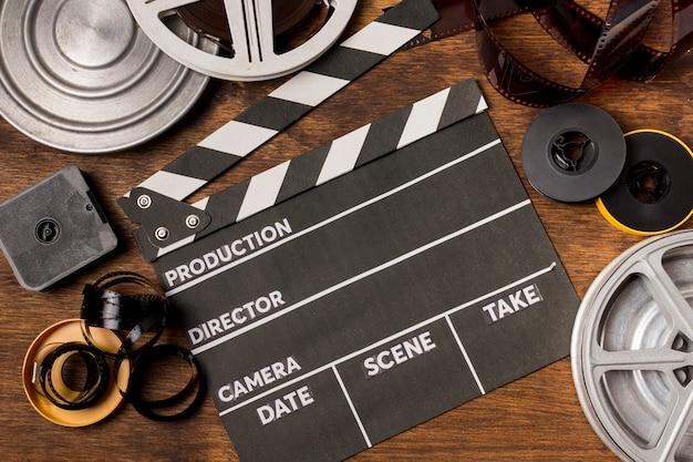 Uma visão elevada da claquete; bobinas de filme; tiras de filme no cenário de madeira