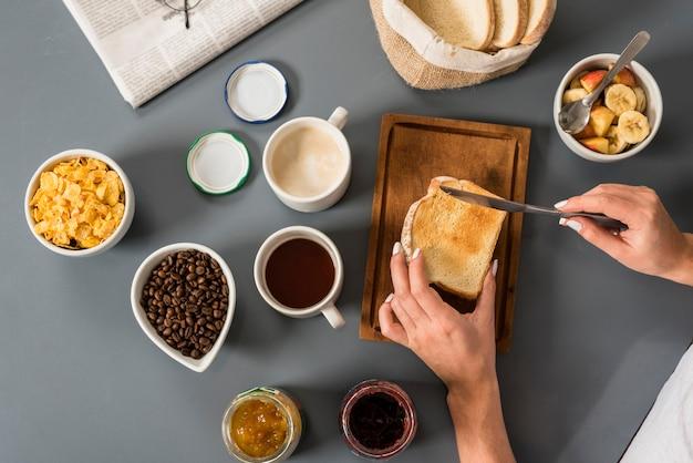 Uma visão elevada da mão da mulher tomando café da manhã