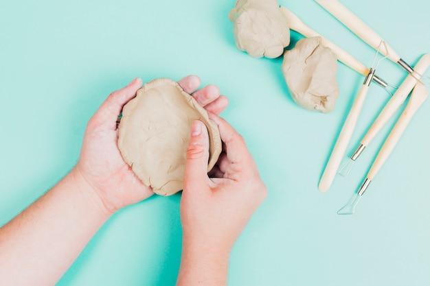 Uma visão elevada da mão humana moldando a argila no pano de fundo verde hortelã
