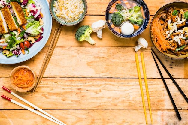 Uma visão elevada da salada tailandesa; brotos; sopa de bola de peixe e macarrão com diferentes tipos de pauzinhos na mesa de madeira