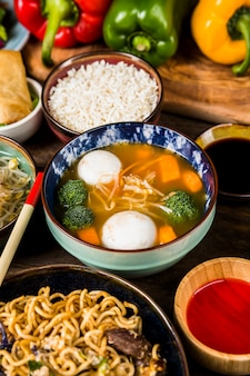 Uma visão elevada da sopa de peixe com arroz; molhos e macarrão