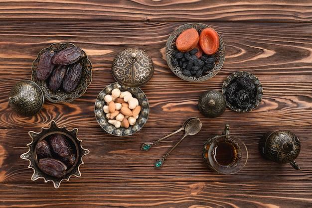 Uma visão elevada das datas frescas do ramadã; nozes; frutas secas e chá na mesa de madeira