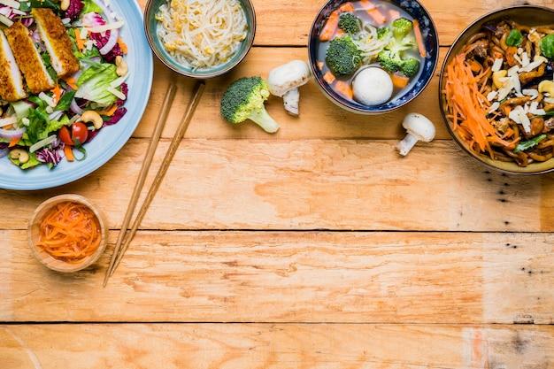 Uma visão elevada de comida tailandesa tradicional com pauzinhos na mesa de madeira