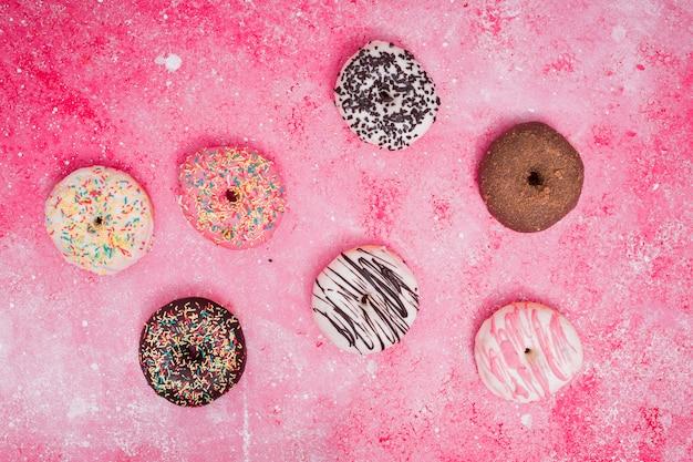 Uma visão elevada de donuts cozidos coloridos no fundo rosa
