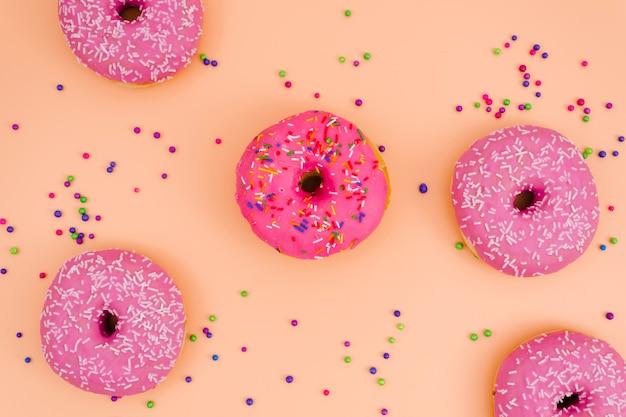 Uma visão elevada de donuts rosa com polvilha bolas no pano de fundo colorido