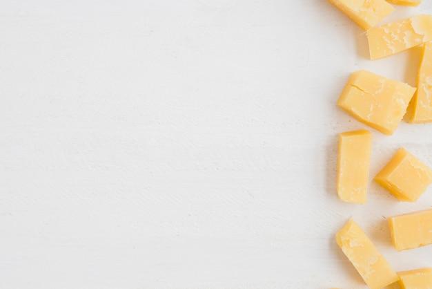 Uma visão elevada de fatias de queijo cheddar em fundo branco