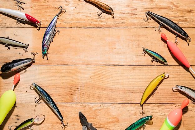 Uma visão elevada de flutuadores de pesca e atrair na mesa de madeira