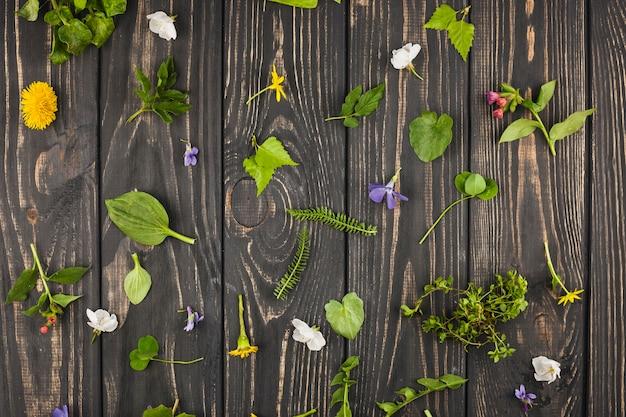 Uma visão elevada de folhas quebradas e flores na mesa de madeira