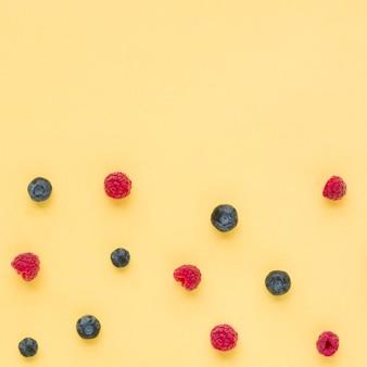 Uma visão elevada de framboesas e mirtilos em fundo amarelo
