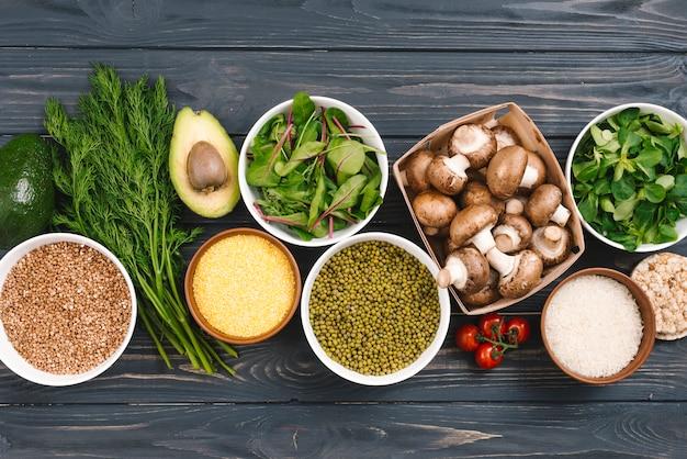 Uma visão elevada de legumes frescos e pulsos na mesa de madeira preta