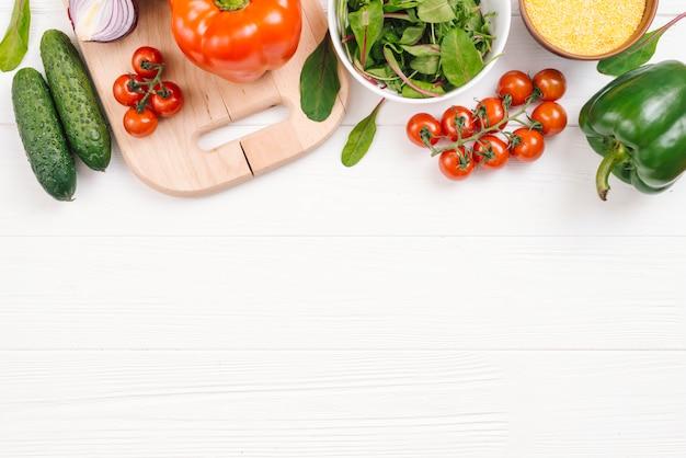 Uma visão elevada de legumes frescos na mesa de madeira branca