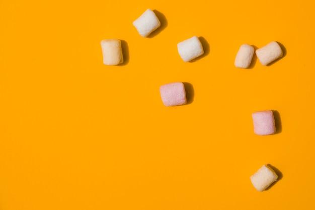 Uma visão elevada de marshmallows em um pano de fundo laranja