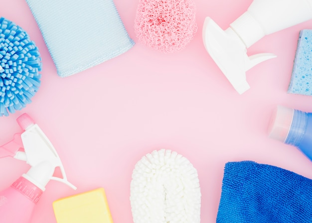 Uma visão elevada de material de limpeza no pano de fundo rosa