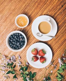 Uma visão elevada de mirtilo; geléia; xícara de morango e café em flores contra o pano de fundo de madeira