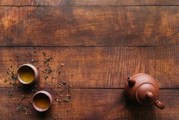Uma visão elevada de panela de barro com xícaras de chá de ervas na mesa de madeira