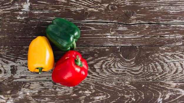 Uma visão elevada de pimentões orgânicos de três cores na mesa de madeira