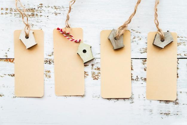 Uma visão elevada de tags com birdhouse em miniatura na mesa branca