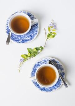 Uma visão elevada de xícaras de chá de porcelana de ervas em pires com galho de limão no fundo branco