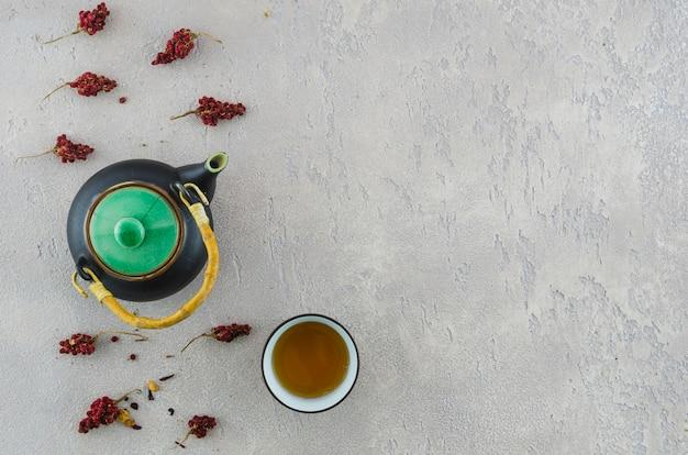 Uma visão elevada do bule oriental e xícara de chá de ervas com ervas no pano de fundo de textura