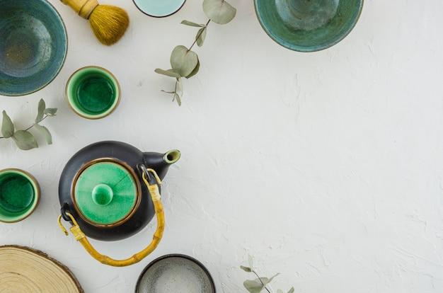 Uma visão elevada do bule; tigela; xícara de chá; escova isolada no pano de fundo branco