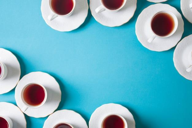 Uma visão elevada do chá de ervas branco em xícara de cerâmica e pires em fundo azul