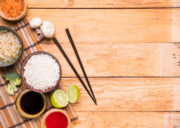 Uma visão elevada do cogumelo; brotar feijão; arroz; brócolis; limão; e molho com pauzinhos contra mesa de madeira