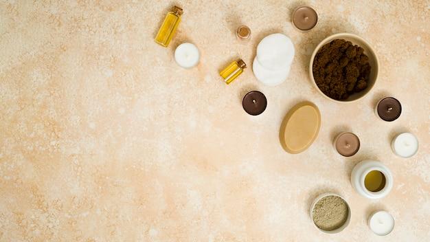 Uma visão elevada do pó de café; sabão de ervas; velas; cotonetes; óleo essencial e pó de argila rhassoul no pano de fundo texturizado bege