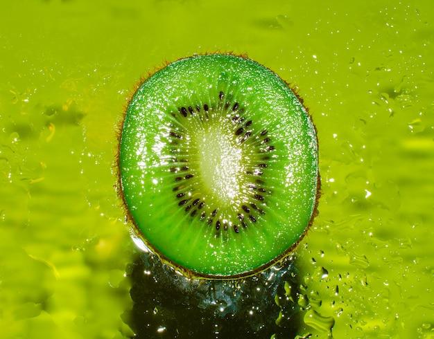 Uma visão em corte transversal de suculento kiwi sobre um fundo verde