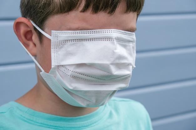Uma visão engraçada de um menino usando máscara médica cirúrgica protetora branca, cobrindo até os olhos para evitar a infecção durante a epidemia, pandemia piada brincadeira rofl.