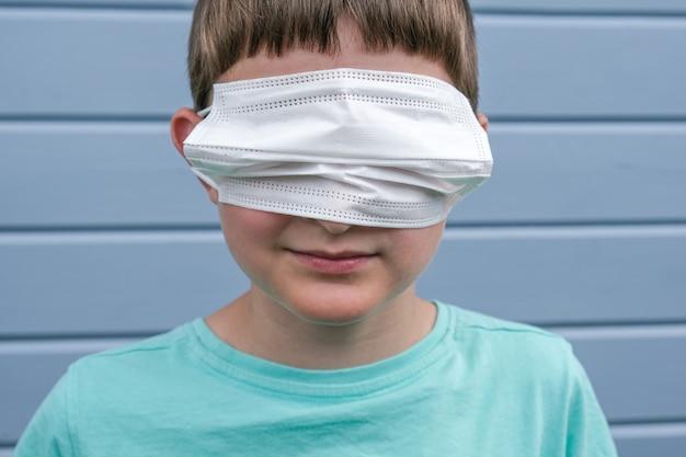 Uma visão engraçada de um menino usando máscara médica cirúrgica protetora branca nos olhos em vez da boca, ele brinca com epidemia e pandemia de covid, rofl.