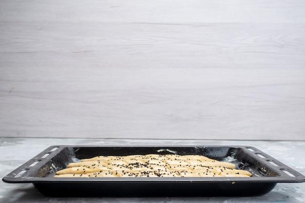 Uma visão frontal da massa de pão cru dentro de uma bandeja preta com óleo sobre a luz da mesa.