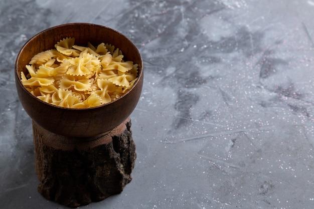 Uma visão frontal da massa italiana crua pouco formada dentro do prato marrom na mesa cinza