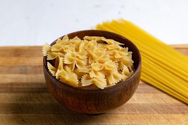 Uma visão frontal da massa italiana crua pouco formada dentro do prato marrom na mesa de madeira