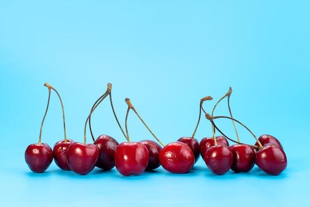 Uma visão frontal das cerejas vermelhas frescas maduras e azedas no azul, cor de frutas do verão
