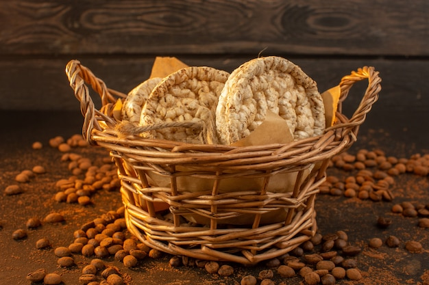 Uma visão frontal das sementes de café marrom com uma cesta de biscoitos e grânulos de grãos de café