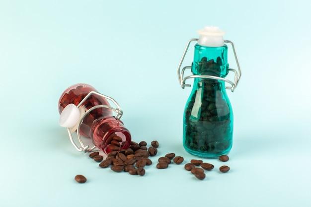 Uma visão frontal das sementes de café marrom dentro de potes de vidro coloridos na superfície azul