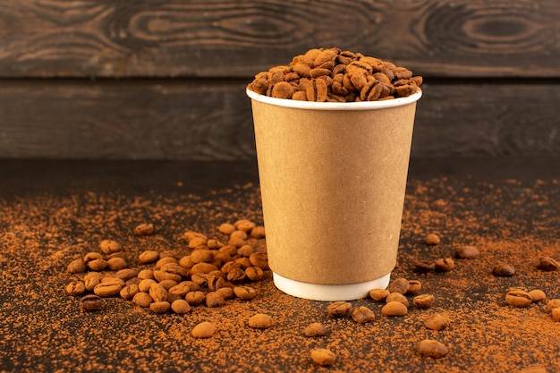 Uma visão frontal das sementes de café marrom dentro de um copo de plástico na superfície marrom e o grânulo de grão escuro da semente de café
