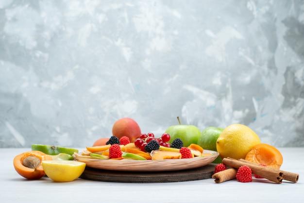 Uma visão frontal de frutas frescas fatiadas maduras e ricas em vitaminas com canela e frutas inteiras na mesa de madeira e fundo branco.