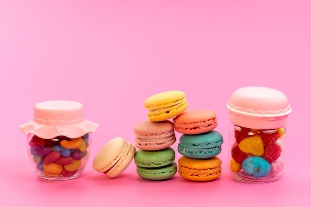 Uma visão frontal de macarons franceses coloridos junto com doces multicoloridos dentro de latas em rosa, confeitaria de biscoito de bolo