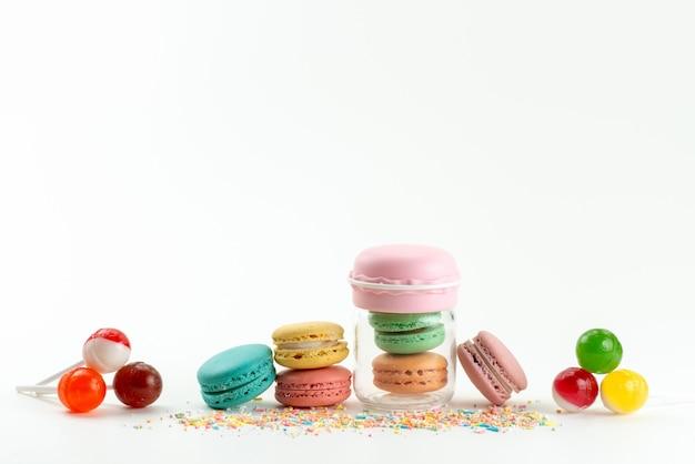 Uma visão frontal de macarons franceses junto com pirulitos em branco, bolo de biscoito com açúcar doce