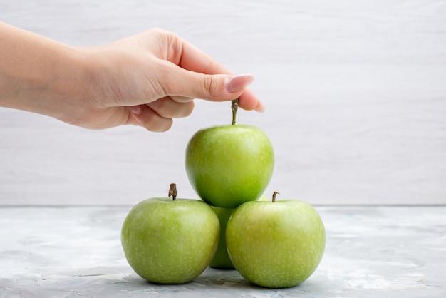 Uma visão frontal de maçãs verdes frescas suaves e suculentas na árvore de mesa clara com frutas frescas