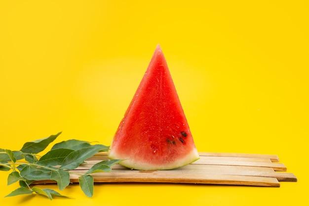 Uma visão frontal de melancia em fatias frescas junto com folhas em frutas de cor marrom de madeira