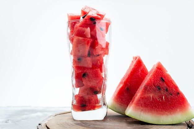 Uma visão frontal de melancia em fatias frescas, suculenta e doce dentro de um copo longo em branco, cor de suco de frutas