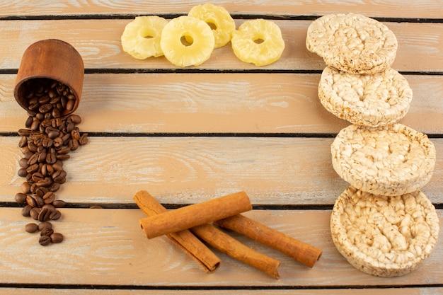 Uma visão frontal de sementes de café com abacaxi seco, canela e biscoitos no creme rústico mesa de café com sementes de café em grão
