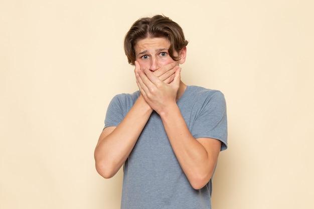 Uma visão frontal de um jovem do sexo masculino com uma camiseta cinza posando segurando a boca