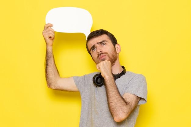 Uma visão frontal jovem do sexo masculino em uma camiseta cinza pensando e segurando uma placa branca na parede amarela.