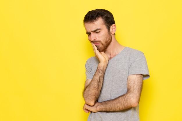 Uma visão frontal jovem do sexo masculino em uma camiseta cinza tendo uma dor de dente na parede amarela.