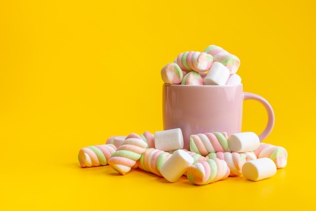 Uma visão frontal mastigar geleias por dentro e por fora em rosa, xícara em amarelo, doce cor de açúcar confiture