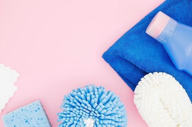 Uma visão geral da esponja; frasco detergente; guardanapo contra o pano de fundo rosa