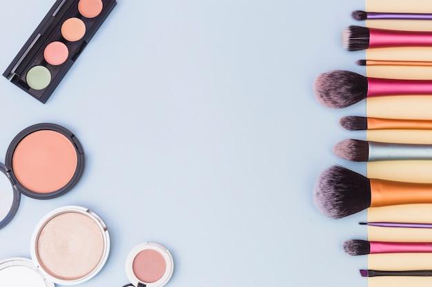 Uma visão geral da paleta de sombras; pincéis de blush e maquiagem em fundo azul